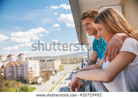 Young Couple Hugging And Enjoying The View From A Balcony - stock photo