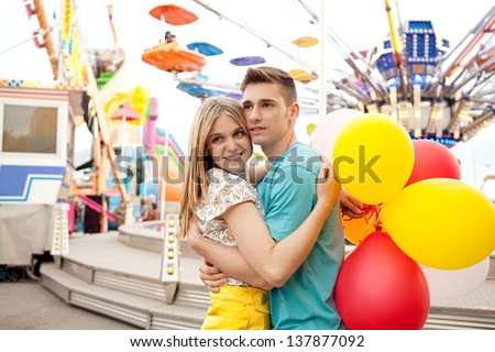 Young couple hugging and holding each other while visiting an attractions park arcade with lights and rides in the background. - stock photo