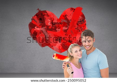 Young couple hugging and holding paint roller against grey room - stock photo