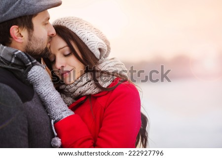 Young couple hugging by the river in winter weather - stock photo