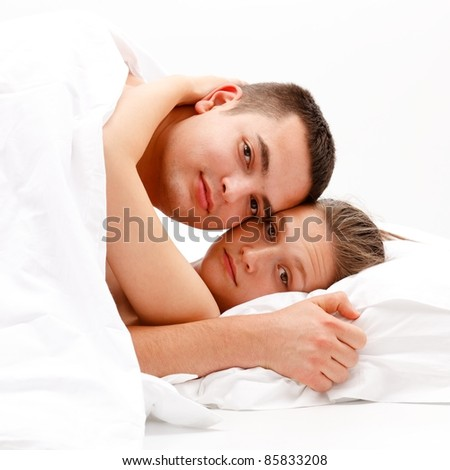 Young couple hugging each other in bed under the quilt