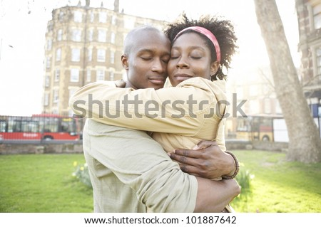 Young couple hugging each other in the city at sunset, smiling.