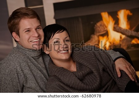Young couple hugging in front of fireplace at home, looking away, smiling. - stock photo