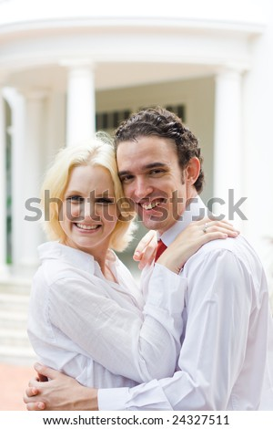 young couple hugging in front of their home