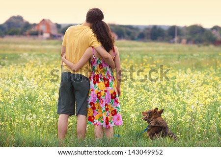 Young couple hugging in the field and looking at the village at sunset. Dog sitting near in the meadow - stock photo