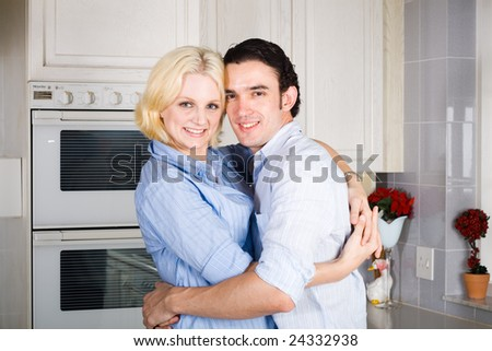 young couple hugging in the kitchen at home - stock photo