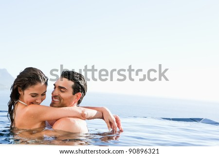 Young couple hugging in the pool - stock photo