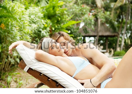Young couple hugging on a sun bed in a villa's tropical garden while on vacation. - stock photo