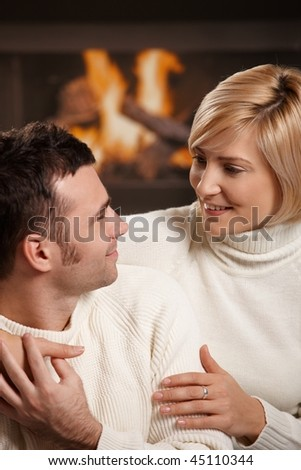 Young couple hugging on sofa in front of fireplace at home, looking at each other, smiling. - stock photo