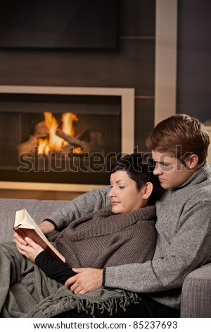 Young couple hugging on sofa in front of fireplace at home, reading book.?