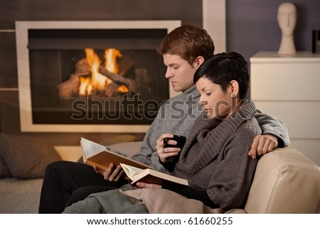 Young couple hugging on sofa in front of fireplace at home, reading books.