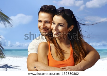 Young couple hugging on the beach, having fun, enjoying summer holiday, looking away.