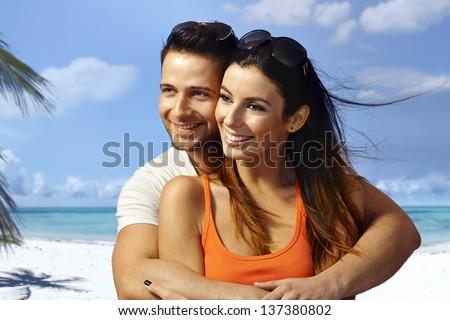 Young couple hugging on the beach, having fun, enjoying summer holiday, looking away. - stock photo
