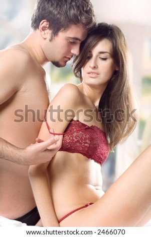 Young couple hugging on the bed in bedroom, in passion - stock photo
