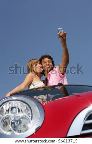 Young couple in a car taking a photography with a mobile phone - stock photo