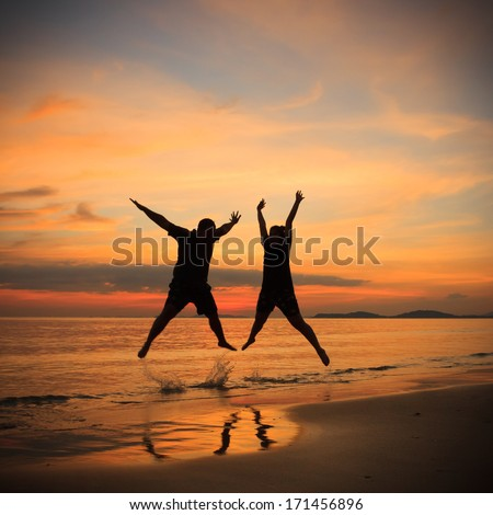 Young couple in a jump on the sea beach at sunset. - stock photo