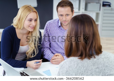 Young couple in a meeting with an adviser or business colleague listening intently to what she is saying , view over the advisers shoulder of the young man and woman - stock photo