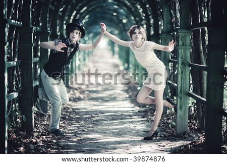 Young couple in a park with long passage. Contrast colors. - stock photo