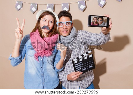 Young couple in a Photo Booth party with gesture face  taking selfie, - stock photo