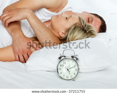 Young couple in bed with focus in alarm clock