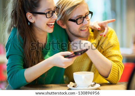 Young couple in cafe, laughing - stock photo