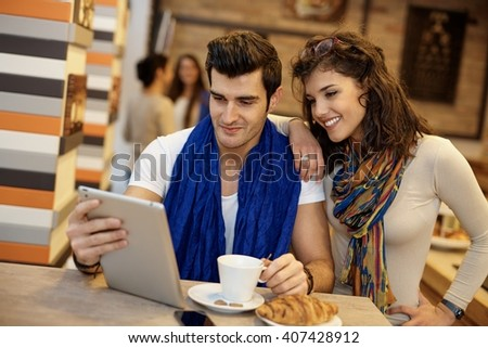 Young couple in cafeteria using tablet computer, smiling.