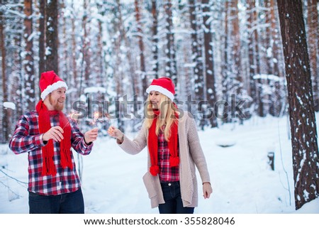 young couple in Christmas hats with sparklers in the winter forest - stock photo