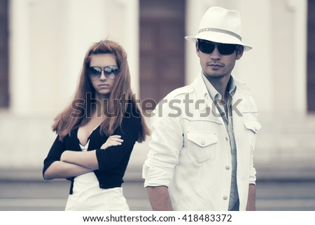 Young couple in conflict on city street. Male and female fashion model in sunglasses. Stylish man and woman outdoor
