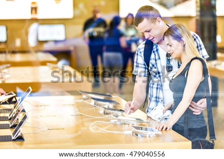 Young couple in consumer electronics retail store browsing at displayed latest tablets, choosing new device.