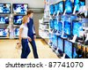 Young couple in consumer electronics store looking at latest television - stock photo