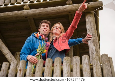 Young couple in Dutch observation hut with flag - stock photo