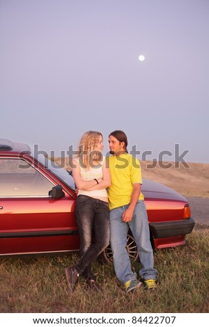 Young  couple in early summer evening with vintage car