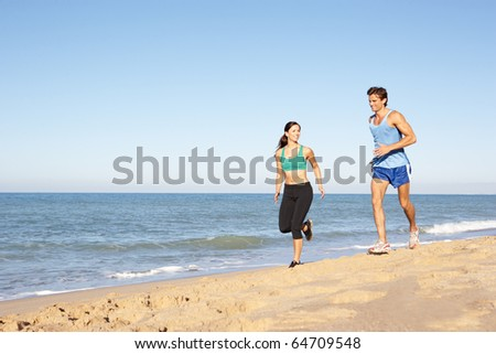 Young Couple In Fitness Clothing Running Along Beach