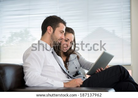 Young couple in formal clothes reading from a tablet - stock photo