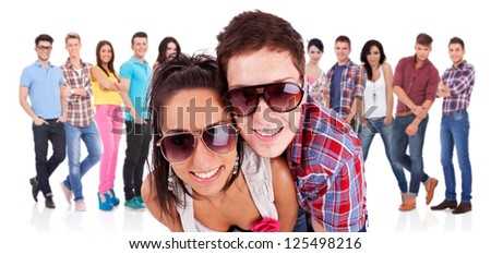 young couple in front of a large group of casual fashion people - stock photo