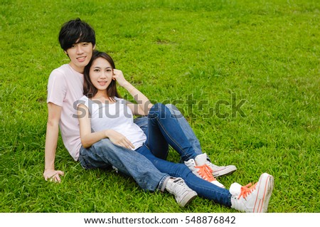 Young couple in jeans in the park sitting on the grass