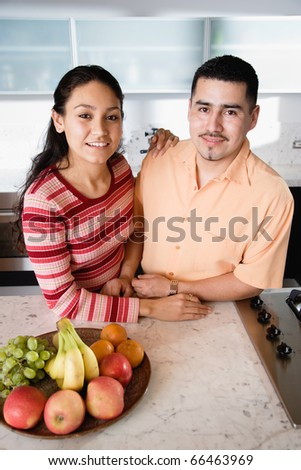 Young couple in kitchen looking at camera - stock photo