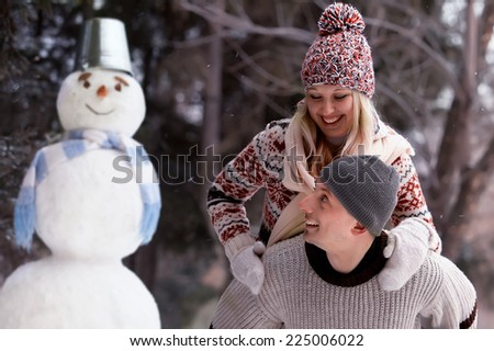 Young couple in knitted hats and sweaters to have fun and laughs next to the snowman - stock photo