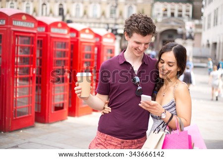 young couple in London checking their phone with a coffee and shopping bags - stock photo