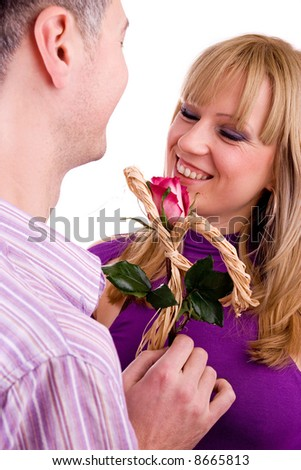 young couple in love (a young man hiding a red rose behind his back in preparation of giving it to a young woman - focus on rose), isolated on white background