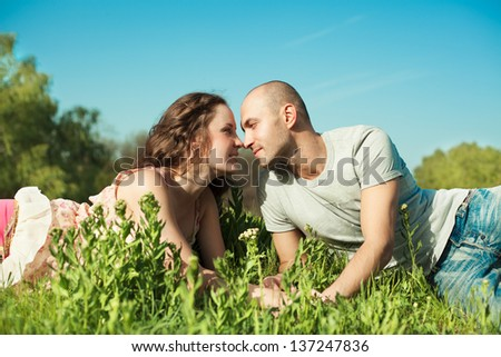 Young couple in love at the park lying on the grass looking at each other - stock photo