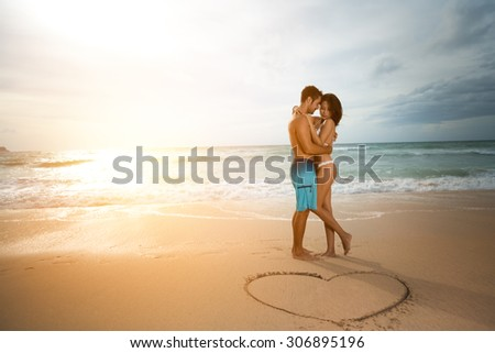 Young couple in love, attractive men and women enjoying romantic date on the beach at sunset. - stock photo