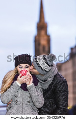 Young couple in love embracing and drinking hot drink from red cup on Royal Mile in Edinburgh. Boyfriend kisses his girlfriend. - stock photo