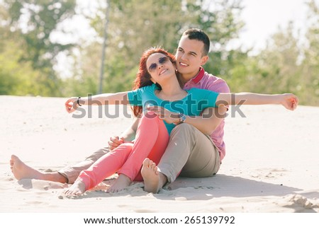 Young couple in love enjoying sunny day o the beach - stock photo