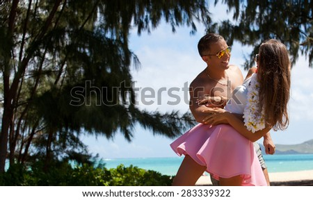 Young couple in love feeling happy on Waimanalo Beach Park, Oahu, Hawaii, USA. Vacations And Tourism Concept. Summer luxury vacation in Hawaii. - stock photo