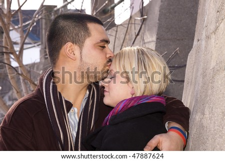 Young couple in love .He is giving her a kiss on the forehead. - stock photo
