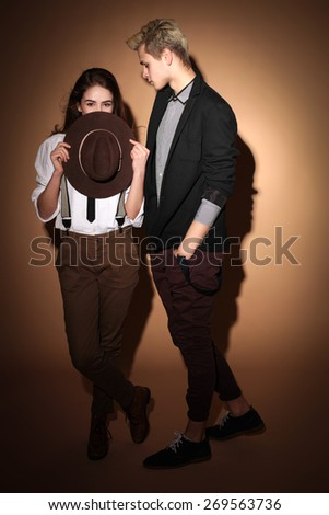 young couple in love hipsters in the studio wearing hats, love, youth, relationships, teenagers - stock photo