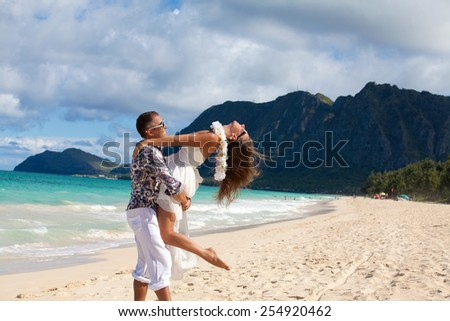 Young couple in love, holding each other tightly in front of the sea. Beach couple having fun on romantic travel honeymoon vacation, summer holidays romance. Young happy lovers.