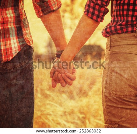 Young couple in love holding hands, tranquil scene, face is not visible. Vintage image - stock photo