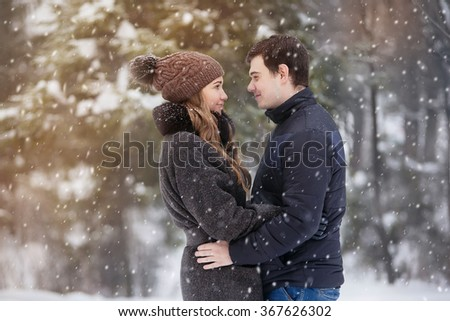 Young couple in love in the winter forest - stock photo